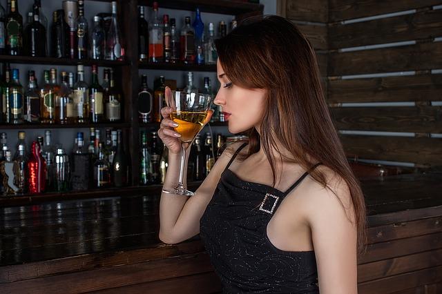 dívka při pití vína u baru
